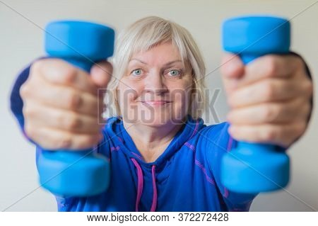 Senior Woman In Blue Doing Her Exercises With Dumbbells. Portrait Of Smiling Elderly Woman With Dumb