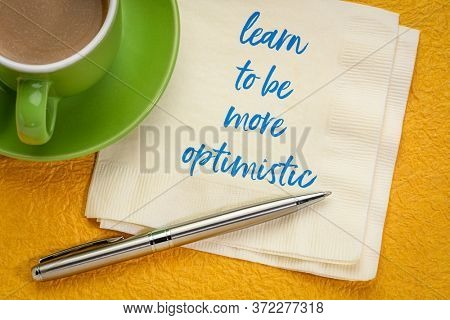 learn to be more optimistic inspirational message - handwriting on a napkin with a cup of coffee, positive mindset and personal development concept