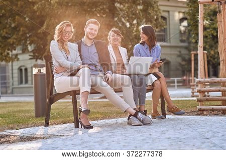 young caucasian adults laughing at bench in a park with their cell phones, laptop, tablet. Looking at camera, eye contact. Break, pause from work.