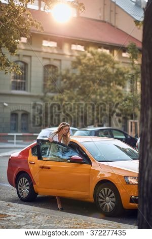 Businesswoman getting into yellow cab on the street