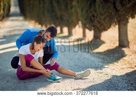beardy young male personal trainer comfort and advising female who injured her ankle on jogging, because she didn't worm up and stretch before training