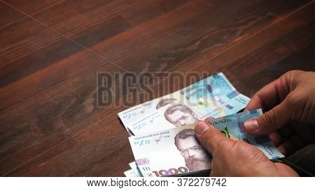 Man Considers Of New Ukrainian Paper Money. He For First Time Sees New Notes In Face Value Of 1000 H