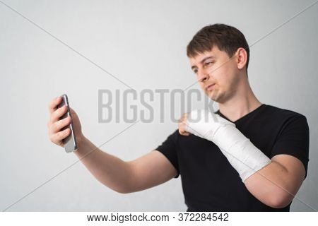 Telemedicine. Broken Arm. Patient With Bone Fracture Communicates On Video Call With Doctor And Show