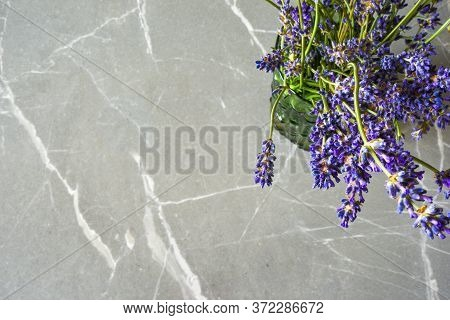 Posy Of Lavender Flowers On An Empty Marble Desk