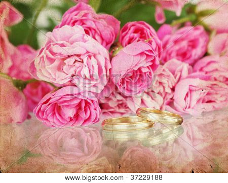Pink roses an wedding ring on vintage background