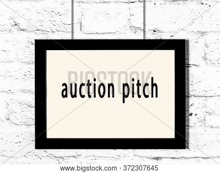 Black Wooden Frame With Inscription Auction Pitch Hanging On White Brick Wall