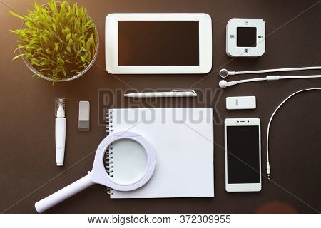 Home Office. Office Workplace With Laptop, Notebook, Office Supplies And Stationery On Dark Brown Ba