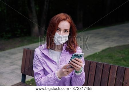 Ginger Girl In Protective Mask Sitting In A Park. Revival After Covid 19 Quarantine