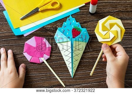 In The Hands Of A Child Origami Paper Ice Cream And Lollipop On A Wooden Table. Children's Art Proje