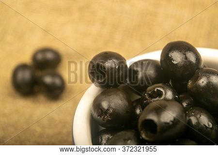 Black Seedless Olives In A Ceramic Bowl And A Few Scattered Olives On A Background Of Coarse-texture