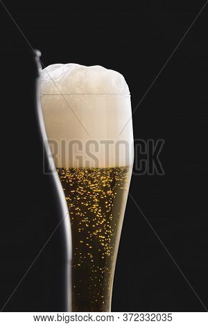 Glass Of Pilsner Beer With Foam And A Bottle Silhouette. German Traditional Beer. Cold Ale In A Long