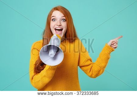 Surprised Young Redhead Woman Girl In Yellow Sweater Posing Isolated On Blue Turquoise Wall Backgrou