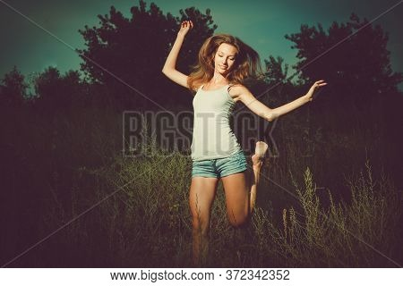 Joyful Ypung Lady Doing Ecstatic Ballet Outside In The Tall Grass