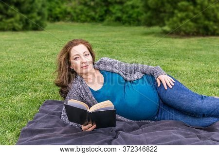 Pregnant Woman Is Reading A Book On A Green Field In A Park.