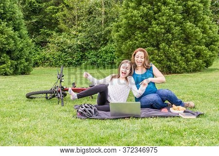 Beautiful Pregnant Woman And Her Daughter Are Laughing In A Summer Green Park With Laptop And Bicycl