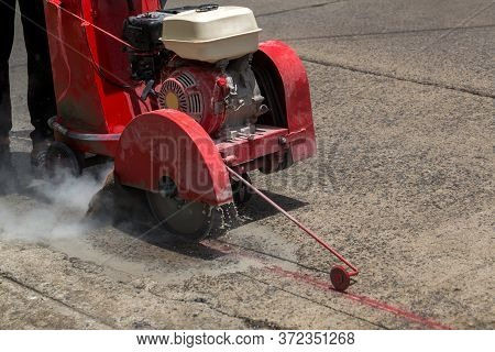 Concrete Road Cutters With Worker. Worker Using Diamond Saw Blade Machine Cutting Concrete Road At C