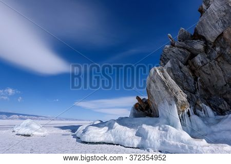 Cape Burhan On Shamanka Rock In Olkhon Island Covered With Icicles In Sunny March Day. Lake Baikal W