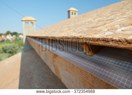 A Close-up On Plywood Board, Osb Used For Roof Sheathing Installed On Roof Beams With Blurred Roofin