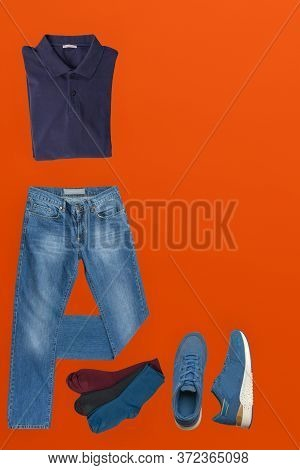 Flat Lay, Mens Fashion.blue Jeans , Blue Sneakers, Dark Blue T-shirt, Different Colors Socks On Orng