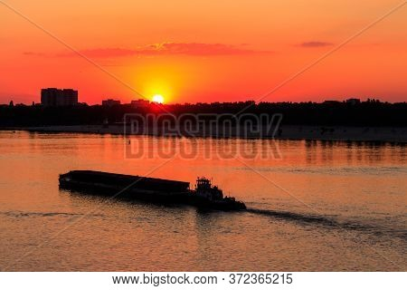 Tugboat Pushing A Heavy Long Barge On The River Dnieper At Sunset