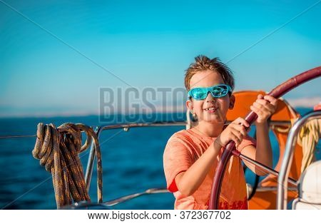 A Handsome Boy Of 9-10 Years Old At The Helm Of A Yacht In Bright Orange Clothes, Blue Sunglasses Ag