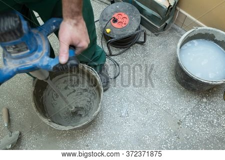 Electric Stirrer. Mixing Cement Based Adhesive. A Professional Construction Worker. A Bucket Full Of