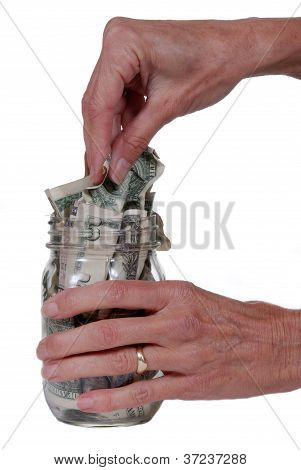 Hand Taking Cash From Jar