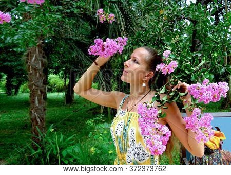 A Young Woman In A Colorful Sundress Under The Blossoming Branches Of A Tree In A Tropical Park
