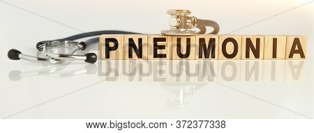 Pneumonia The Word On Wooden Cubes, Cubes Stand On A Reflective White Surface, On Cubes - A Stethosc