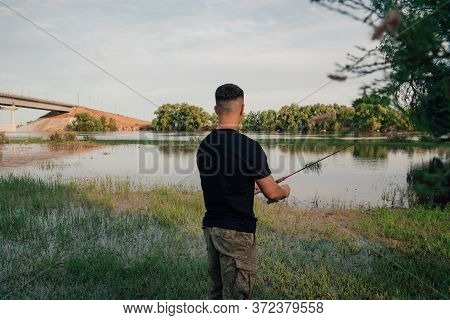 Fishing In River.a Fisherman With A Fishing Rod On The River Bank.
