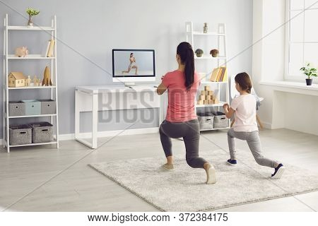 Family Does Exercises Online. Mother And Daughter Watch Online Fitness Trainer Video Course In Room
