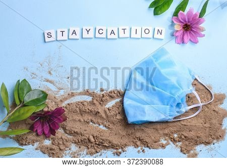 Beach Sand On A Blue Background With Wood Letters And A Word Staycation.