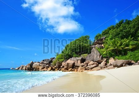 Petite Anse beach with big granite stones in La Digue Island, Seychelles. Tropical landscape with sunny sky.