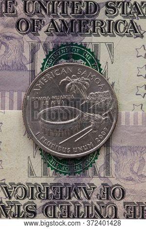 A Quarter Of American Samoa On Us Dollar Bills. Symmetric Composition Of Us Dollar Bills And A Quart