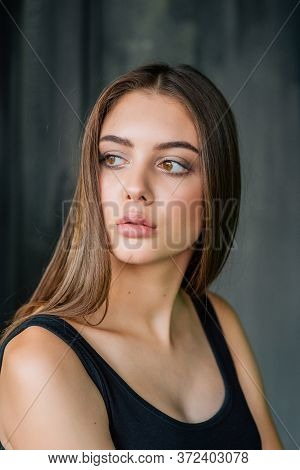 Beauty Portrait Of A Pretty Woman Looking Away Over Gray Background. Beautiful Girl Looks Away On A