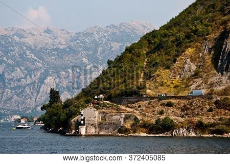 The View From The Water To The Mountainous Shore On A Highway And The Small Navigation Beacon On The