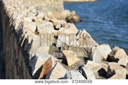 Rough Sharp Rock Retaining Wall Along The Coast.