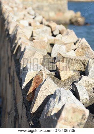 Sharp Jagged Rocks With A Coastal Retaining Wall.