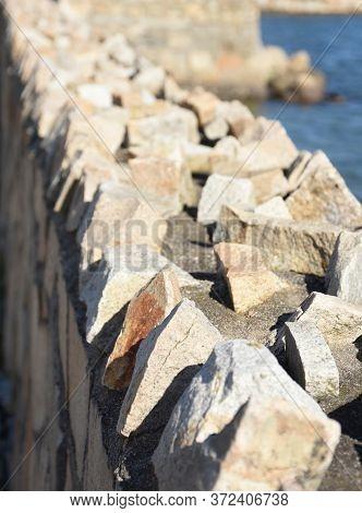 Sharp Jagged Rocks Along The Top Edge Of A Retaining Wall.