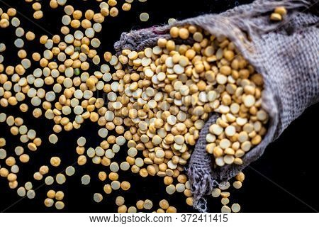 Close Up Shot Of Raw Chickpea Lentil/yellow Lentil In A Gunny Bag On A Black Shiny Surface