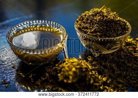 Shot Of Raw Dried Kasuri Methi Along With Its Freshly Prepared Paste In A Glass Bowl On A Black Shin