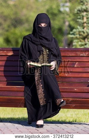 A Migrant From The Middle East Is Sitting On A Bench. Arab Woman Black National Dress Is Reading A B