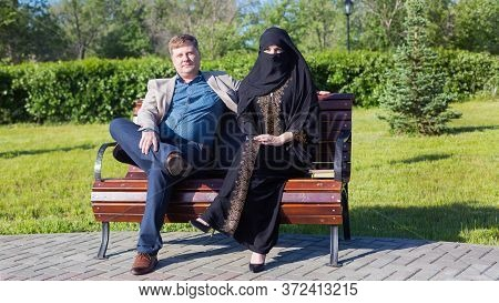 Caucasian Man And Islamic Woman Chatting On The Street. A European Adult Man Tells A Funny Story To