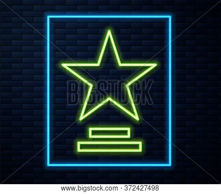 Glowing Neon Line Movie Trophy Icon Isolated On Brick Wall Background. Academy Award Icon. Films And