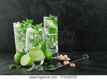 Glasses Of Mojito Refreshing Summer Cocktail With Ice Cubes Mint And Lime On Black Board With Spoon