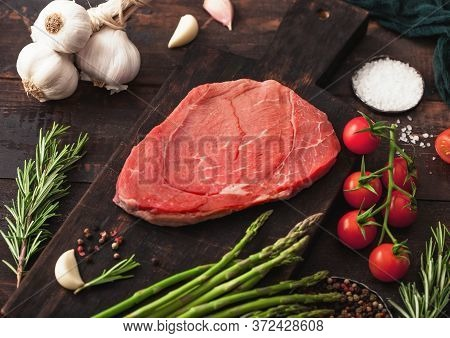 Raw Fresh Beef Braising Steak On Chopping Board With Garlic, Asparagus And Tomatoes With Salt And Pe