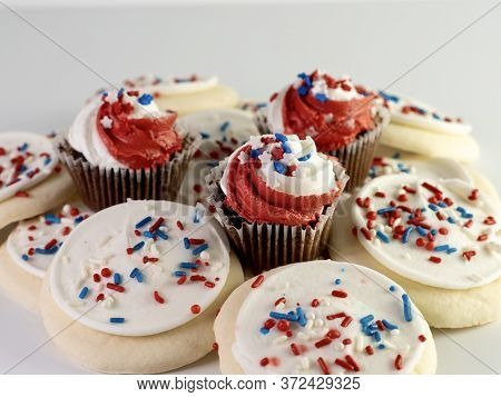 White Sugar Cookies With Red, White And Blue Sprinkles With 3 Mini Chocolate Cupcakes With Red And W