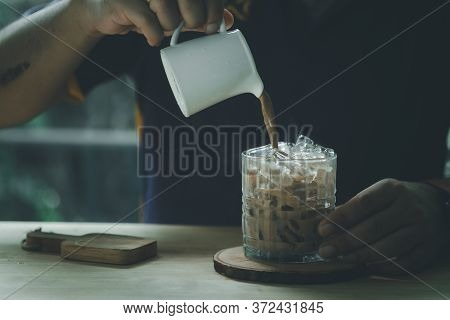 Person Pouring Cold Mocha In A Glass With Ice Cubes In The Morning