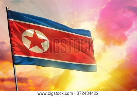 Fluttering Democratic Peoples Republic Of Korea (north Korea) Flag On Beautiful Colorful Sunset Or S