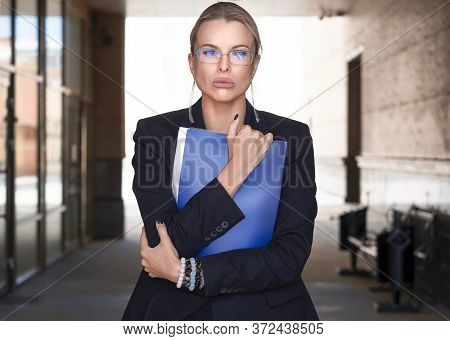 A Close Portrait Of A Woman With Eyeglasses In A Business Suit Holds Tightly A Folder With Important